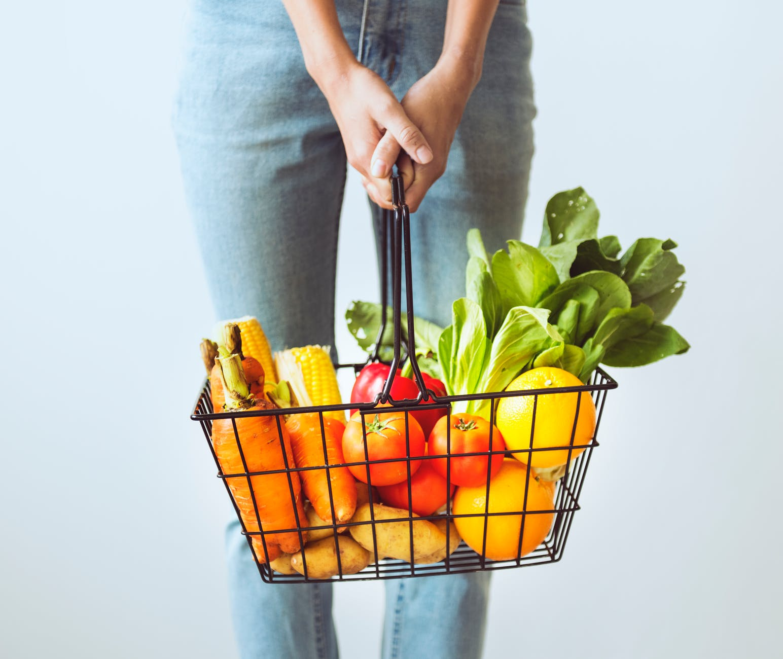 person carrying basket of vegetables